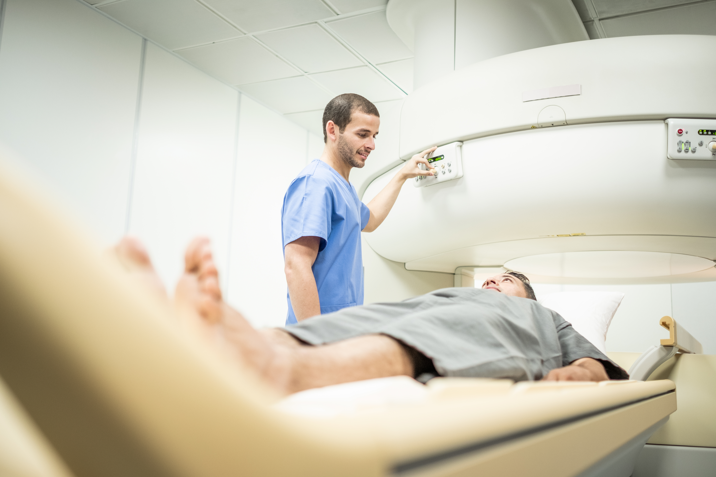 Technician preparing patient for MRI scan