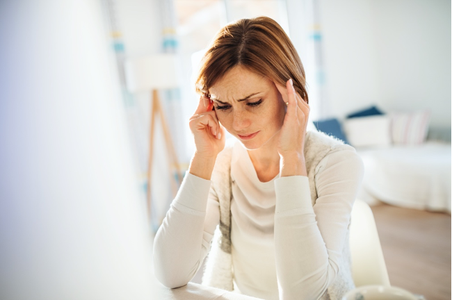 A woman sitting at desk in pain
